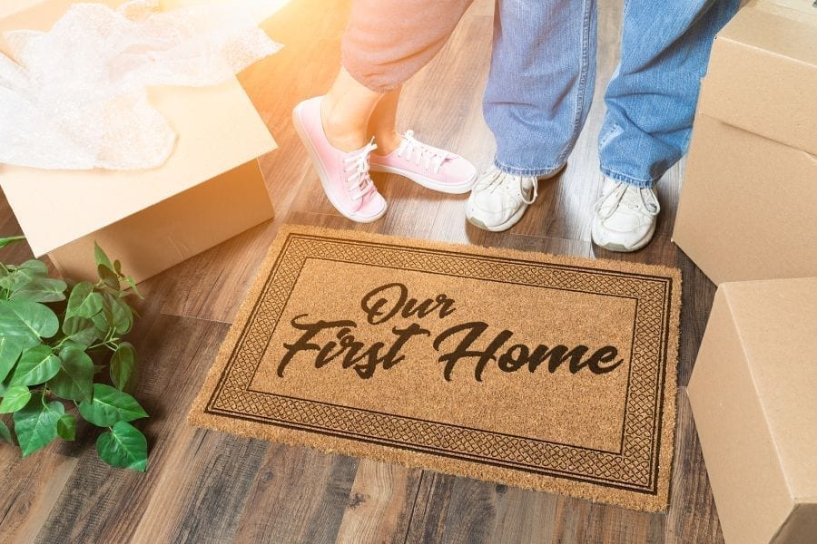 first home buying, Man and Woman Unpacking Near Our First Home Welcome Mat, Moving Boxes and Plant,burleigh waters, robina, palm beach first home owners, fhog, first home owner grant, saving for first home